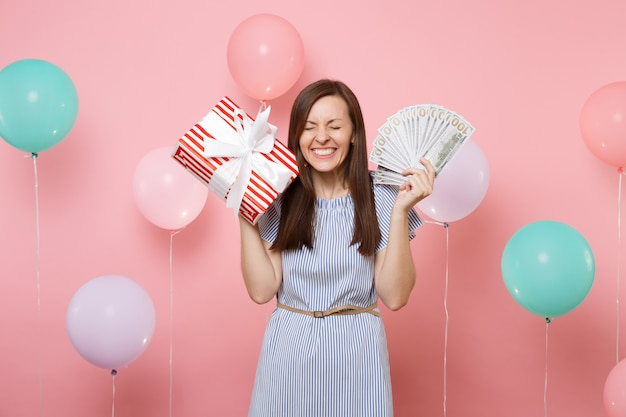 Portrait of overjoyed happy woman in blue dress holding bundle lots of dollars cash money and red box with gift present on pink background with colorful air balloons. birthday holiday party concept.