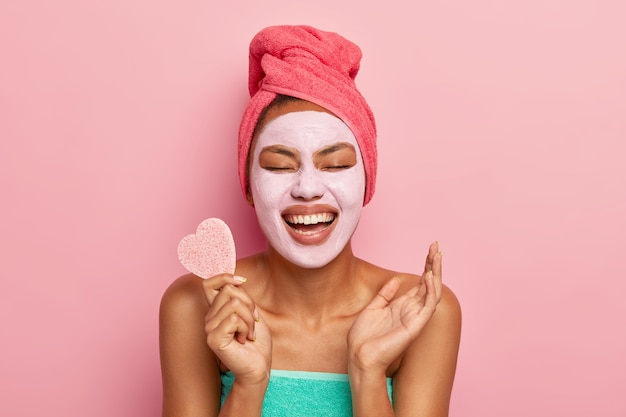 Portrait of overjoyed woman laughs happily, holds cosmetic sponge, raises palm being in high spirit, wears clay mask on face for removing wrinkles and clog pores, stands alone over pink wall