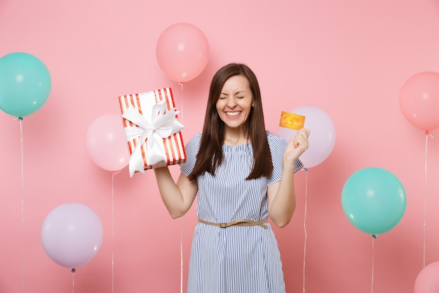 Portrait of overjoyed woman with closed eyes in blue dress hold credit card and red box with gift present on pink background with colorful air balloon. birthday holiday party, people sincere emotions.