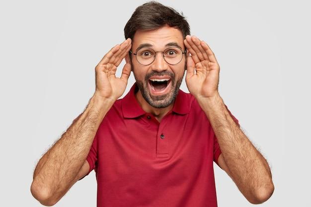 Ritratto di giovane hipster maschio barbuto felicissimo tiene le mani vicino alla testa, ha un'espressione gioiosa, si diverte insieme agli amici, apre ampiamente la bocca, ride positivamente, isolato su un muro bianco.