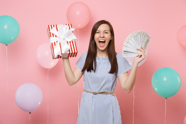 Portrait of overjoyed young woman in blue dress holding bundle lots of dollars cash money and red box with gift present on pink background with colorful air balloons. birthday holiday party concept.
