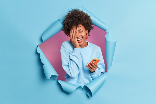 Portrait of overjoyed young woman makes face palm smiles broadly keeps eyes closed uses smartphone for texting expresses positive authentic emotions breaks through blue paper wall