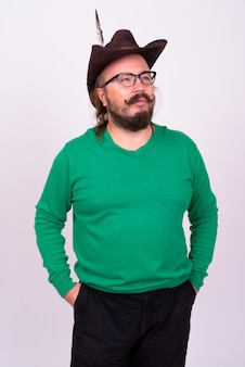Portrait of overweight bearded man with mustache and long hair wearing green sweater against white wall