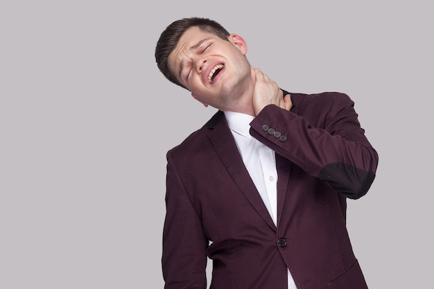 Portrait of painful sick handsome young businessman in violet suit and white shirt, standing with closed eyes and feeling pain on his neck. indoor studio shot, isolated on grey background.