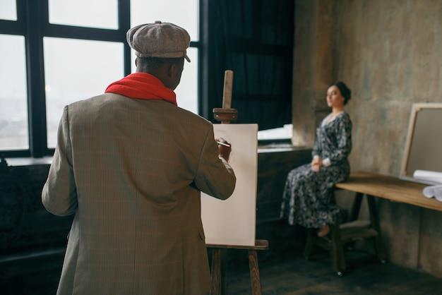 ブラシ付きの肖像画家は女性モデルを描きます。彼の職場に立っている男性アーティスト、ワークショップのイーゼルでクリエイティブマスター