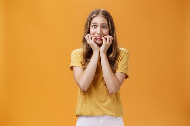 Ritratto di giovane donna insicura sciocca e nervosa che si sente spaventata tremando dalla paura che si morde le unghie tenendo le dita in bocca fissando la telecamera spaventata su sfondo arancione.