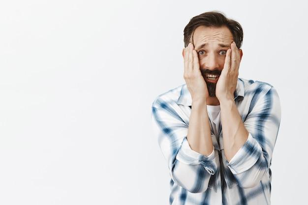 Portrait of panicking bearded mature man posing