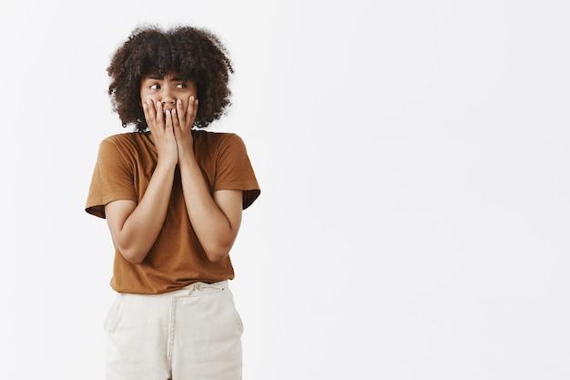 Ritratto di panico timido e insecuto carino modello femminile dalla pelle scura con i capelli ricci che tiene i palmi delle mani sulla bocca per non urlare sensazione di ansia o nervosismo a destra