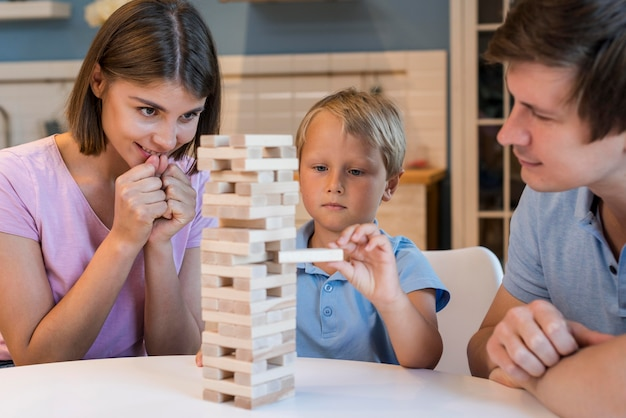 Portrait of parents playing jenga with son