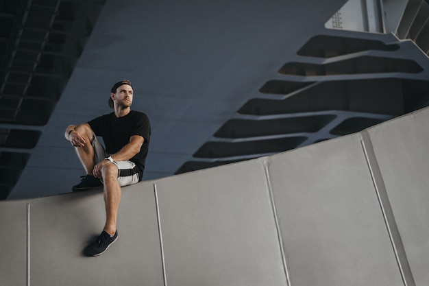 Portrait of parkour athlete sitting on edge of the wall after hard freerunning