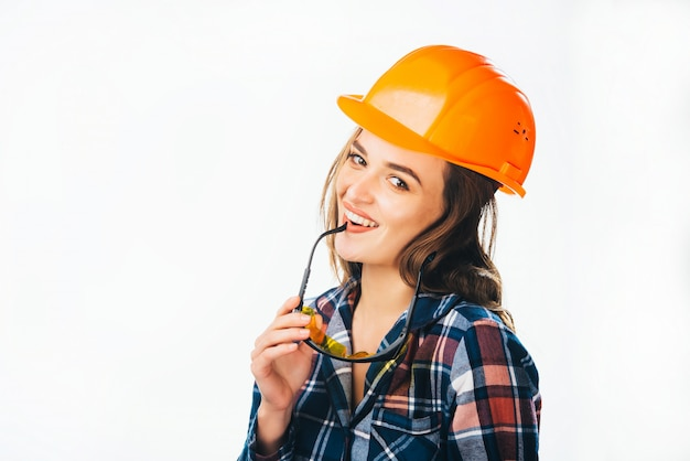 Portrait of passionate female builder with helmet and glasses touching her lips