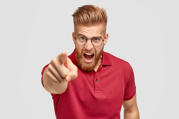 Portrait of peevish bearded guy with ginger trendy hairstyle, yells angrily at somebody, points with index finger directly at camera