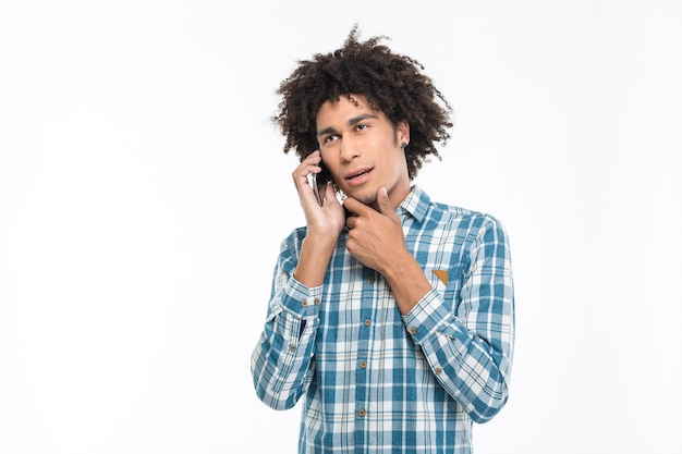 Portrait of a pensive afro american man talking on the phone isolated on a white wall