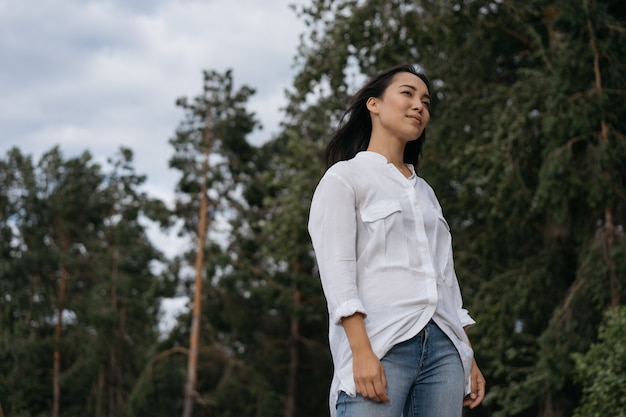 Portrait of pensive asian woman breathing fresh air, looking for inspiration, relaxing outdoors