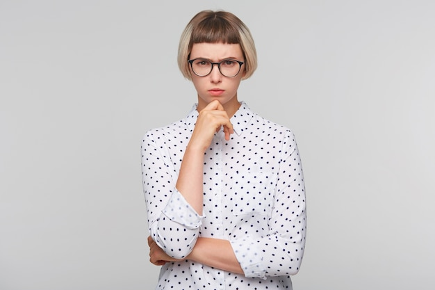 Portrait of pensive attractive blonde young woman wears polka dot shirt
