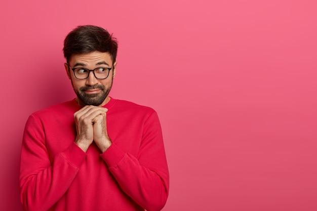 Portrait of pensive bearded man looks aside, keeps hands under chin, gazes with interest away, wears casual bright jumper and spectacles, thinks about something. monochrome. copy space aside for text