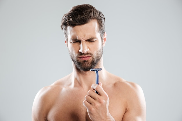 Portrait of pensive bearded naked man looking at razor