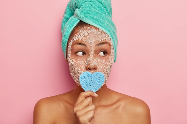 Portrait of pensive beautiful woman with bare shoulders, has scrub facial mask, unclogges pores, keeps sponge on mouth, focused away at right side, has towel on head, poses against pink wall