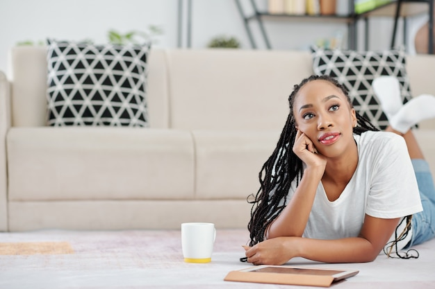 Portrait of pensive beautiful young black woman lying on the floor with cup of coffee and digital tablet