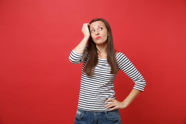 Portrait of pensive bewildered young woman in striped clothes looking up, keeping hand on head