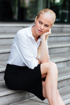 Portrait of a pensive business woman sitting on the stairs outdoors