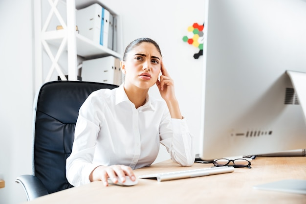 Portrait of a pensive businesswoman sitting at the table in office and looking away