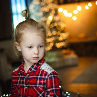 Portrait of pensive cute beautiful girl in checkered red shirt