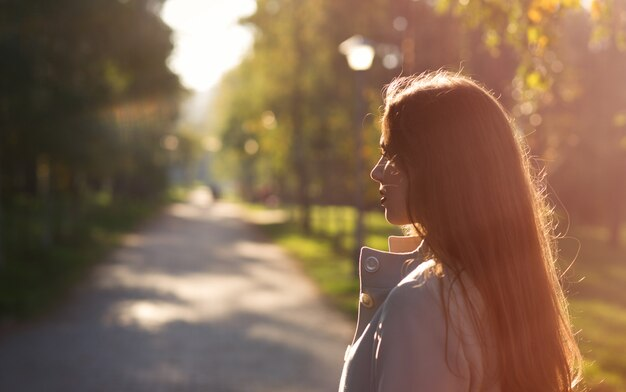 Portrait of pensive girl in sunny autumn park in october.