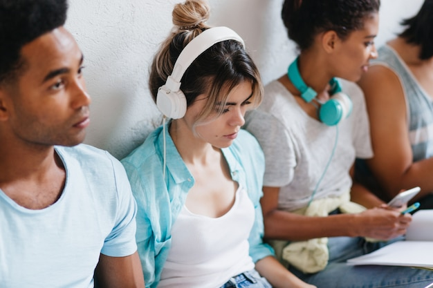 Portrait of pensive girl with trendy hairstyle sitting between friends and listening music in big white headphones. young lady in blue shirt looking down enjoying favorite song.
