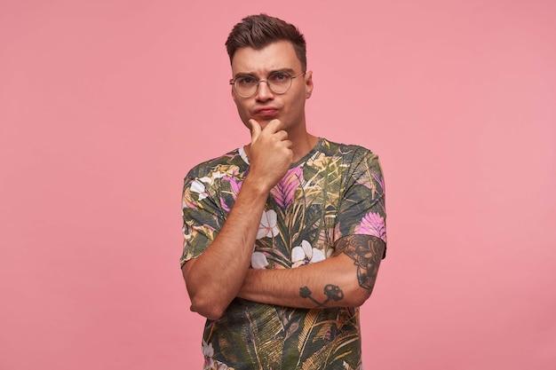 Ritratto di pensieroso bello giovane maschio in t-shirt fiorita con faccia seria, tenendo il mento con la mano e accigliato