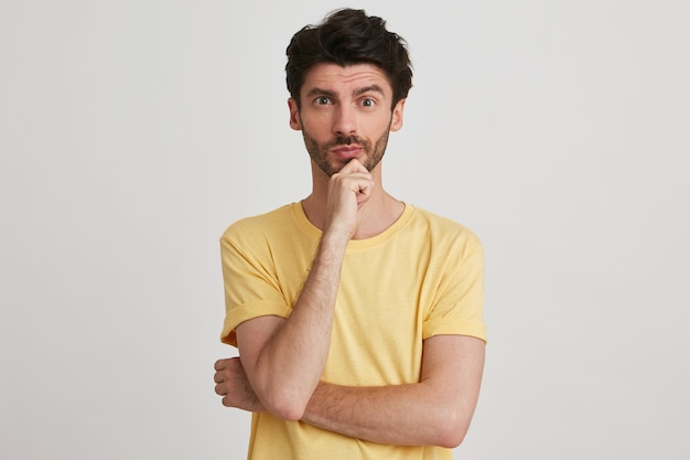 Portrait of pensive handsome bearded young man wears yellow t shirt looks thoughtful, keeps hands folded and thinking isolated on white