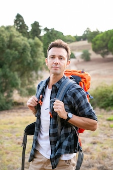 Portrait of pensive male traveler standing on nature. handsome caucasian man traveling and carrying backpack. backpacking tourism, adventure and summer vacation concept