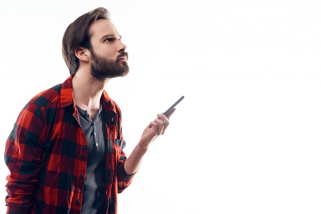 Portrait of pensive man holding phone and looks up