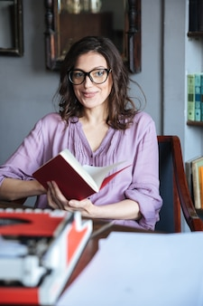 Portrait of a pensive mature authoress in eyeglasses