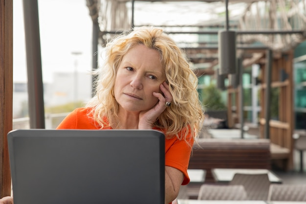 Portrait of pensive mature woman working at laptop in cafe