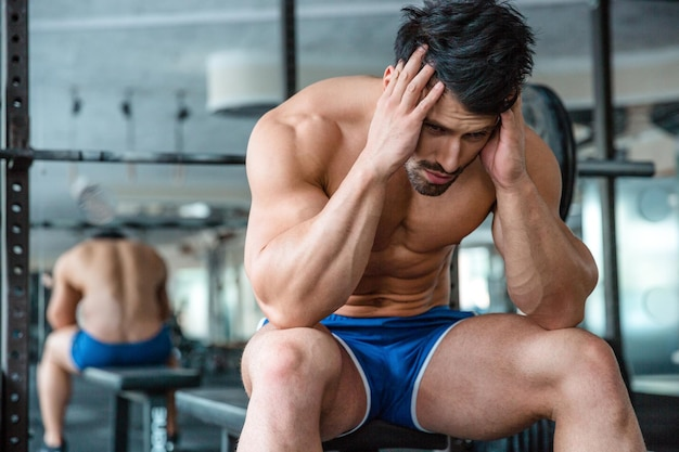 Portrait of a pensive muscular man sitting on the bench in fitness gym