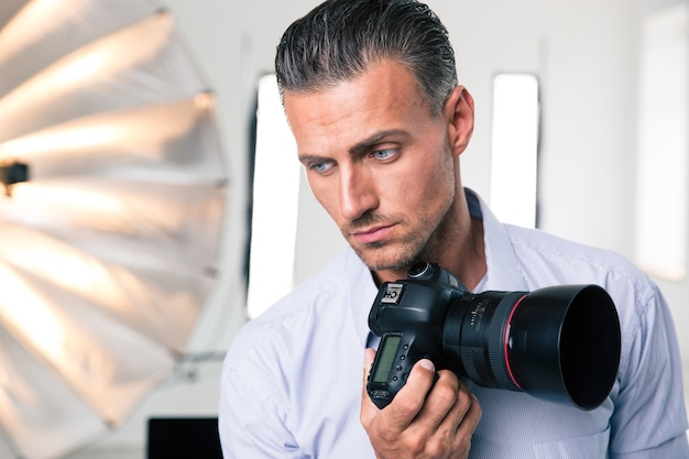 Portrait of a pensive photographer holding camera in studio