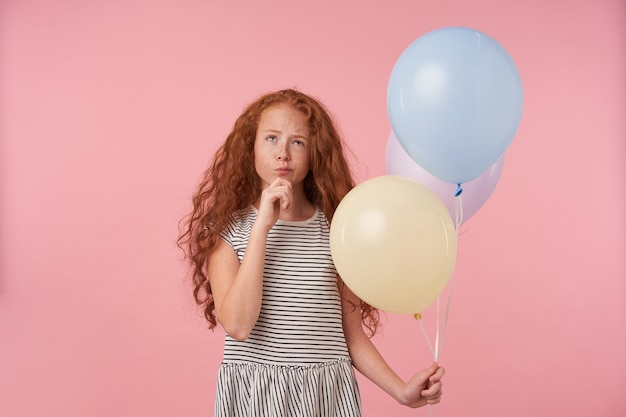 Portrait of pensive redhead curly female kid with air balloons in her hand posing over pink background, keeping hand on her chin and looking upwards thoughtfully, wearing casual striped dress
