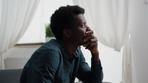 Portrait of pensive thoughtful african american man looking out the window dreaming or thinking at p...
