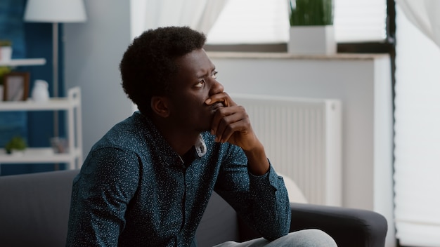 Portrait of pensive thoughtful authentic african american man looking out the window