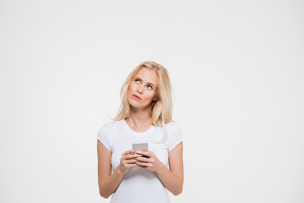 Portrait of a pensive woman holding mobile phone