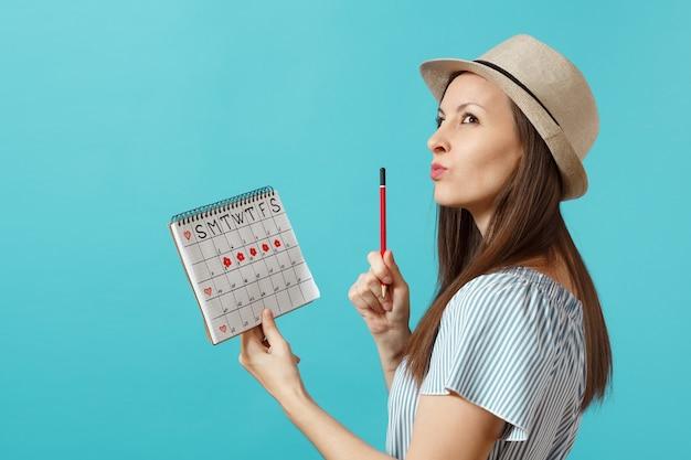 파란 드레스를 입은 초상화에 잠겨있는 여성, 빨간 연필을 든 모자, 파란 배경에 격리된 월경일을 확인하기 위한 여성 기간 달력. 의료 의료, 부인과 개념입니다. 복사 공간