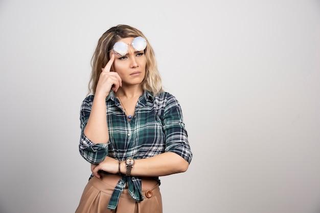 Ritratto di donna pensierosa in posa con occhiali alla moda.