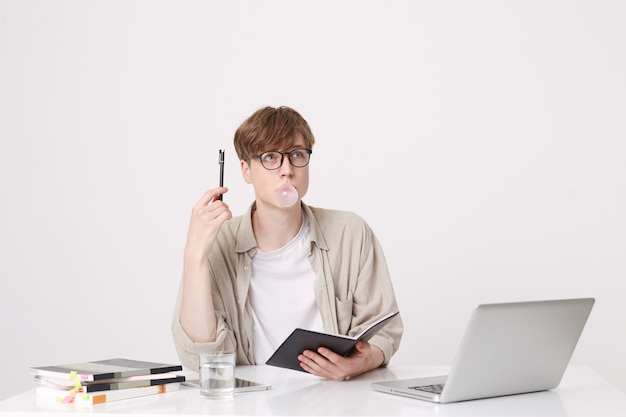 Portrait of pensive young man student wears beige shirt and glasses thinking and blowing bubbles with chewing gum at the table with laptop computer and notebooks isolated over white wall
