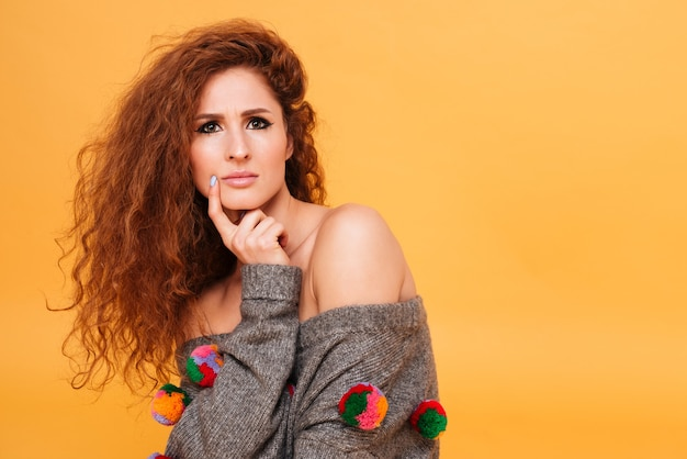 Portrait of a pensive young woman with red hair  isolated over orange wall