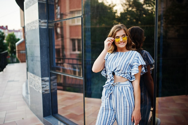Portrait of a perfect young woman wearing striped overall and yellow sunglasses poses on a balcony