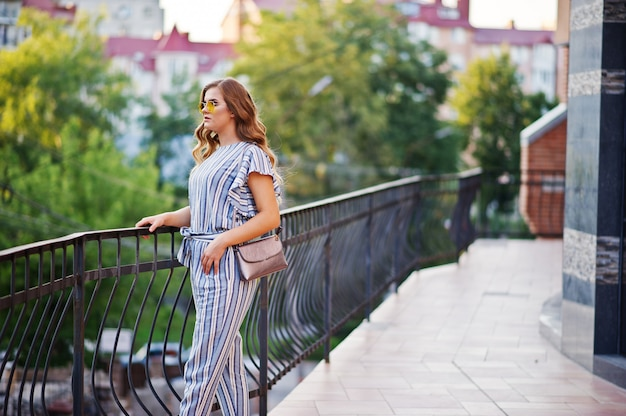 Portrait of a perfect young woman wearing striped overall and yellow sunglasses poses with her handbag on a balcony