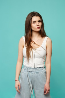 Portrait of perplexed bewildered young woman in light casual clothes looking camera isolated on blue turquoise background in studio. people sincere emotions, lifestyle concept. mock up copy space.