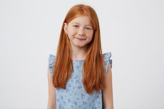 Ritratto di petite carino calma sorridente ragazza dai capelli rossi lentiggini indossa in abito blu, si trova su sfondo bianco.