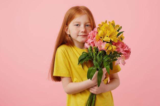 Портрет миниатюрной милой улыбающейся рыжеволосой девушки с веснушками с двумя хвостами, держит букет, носит желтую футболку, стоит на розовом фоне.